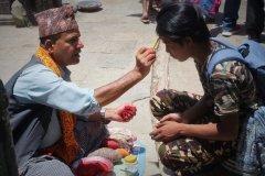 Hindu Brahmane malt Tika (Segenszeichen) auf die Stirn
