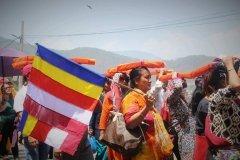 Festzug mit buddhistischer Fahne und heiligen Schriften auf dem Kopf