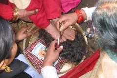 Erster Haarschnitt - Chudakarana - Biraj stellt seine Füsse auf den Opferteller mit den Haaren