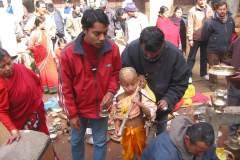 Erster Haarschnitt - Chudakarana -  Birajs verteilt den Puja-Teller auf dem Altar