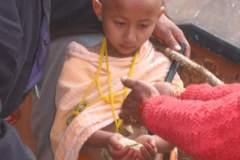 Erster Haarschnitt - Chudakarana -  Biraj bekommt von Angehörigen Reis gespendet