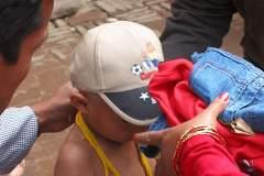 Erster Haarschnitt - Chudakarana -  Biraj erhält als Geschenk eine Jeans und ein Sweatshirt