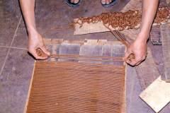 Herstellung tibetischer Räucherstäbchen - Schnüre werden gerade auf Holzbretter gelegt